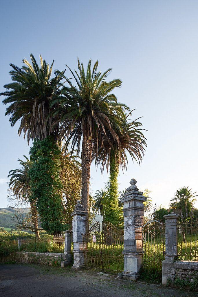 Verja y palmeras en Las Helgueras, concejo de Ribadedeva, Asturias, frente a una casa de indianos