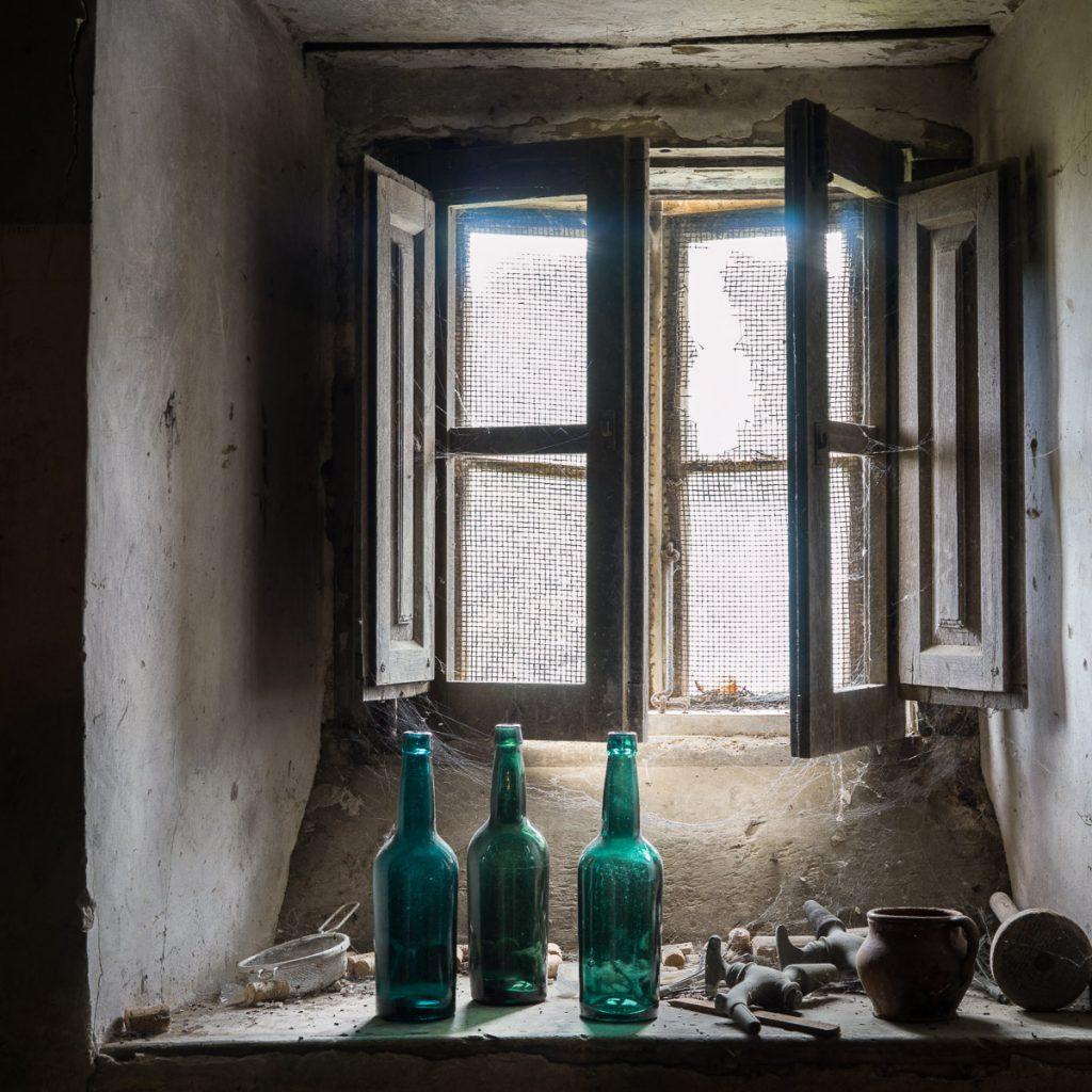 Bodegón de botellas de sidra junto a la ventana de un llagar tradicional en Libardón, Colunga